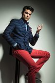 stock photo of stool  - Young handsome fashion man sitting on a stool pointing up - JPG