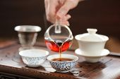 stock photo of brew  - China tea ceremony with puerh tea brewing in haiwan horizontal - JPG