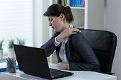 image of muscle pain  - Businesswoman leading sedentary lifestyle causing back pain - JPG