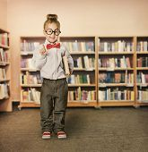 stock photo of book-shelf  - School Kid in Library Child in Glasses with Book Little Girl Student Finger Point Up Bookcase Shelves - JPG