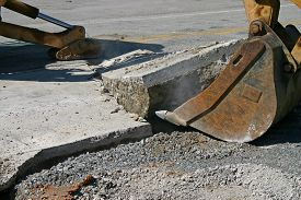 picture of backhoe  - the bucket of a backhoe pulling up concrete pavement - JPG