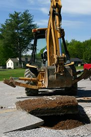 pic of backhoe  - a backhoe lifts a slab of concrete from a roadway - JPG