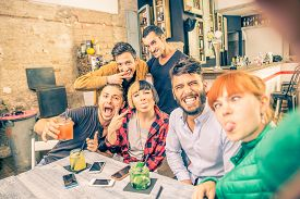 stock photo of selfie  - Group of friends having fun in a cocktail bar and taking a selfie  - JPG