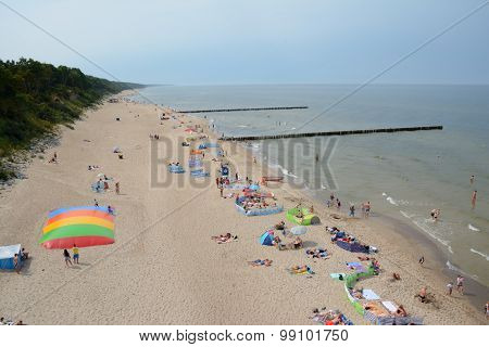 People And Wooden Groynes On Beach In Trzesacz And Rewal, Poland