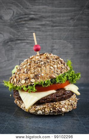 Gourmet hamburger with swiss cheese and fresh vegetables on multigrain bun over dark background