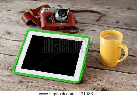 Digital tablet computer with black screen with coffee and vintage camera on wooden background closeu
