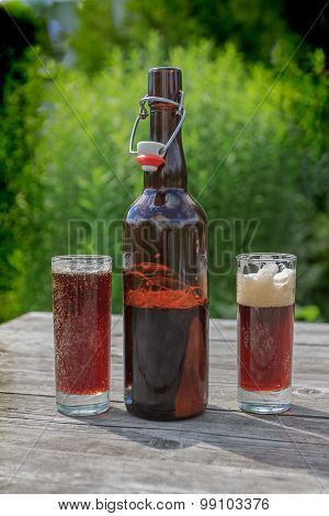 Brown Glass Bottle And Two Tall Glasses Full Of Frothy Dark Beer On Rustic Wooden Table In Summer Ga
