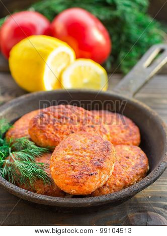 salmon fishcakes in a cast iron skillet, tomatoes and lemon on a dark table
