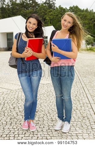 Two beautiful teenage students walking together in the school