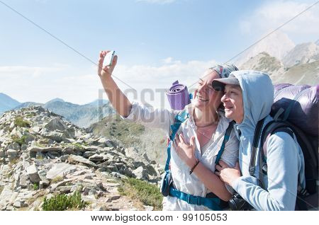 Middle age Friends Taking Selfie at Top of Mountain