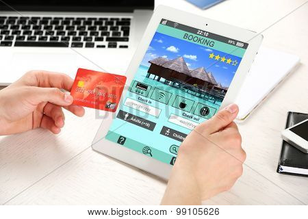 Man holding tablet with screen interface of booking hotels