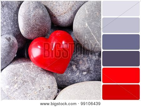 Red heard over pebbles background and palette of colors