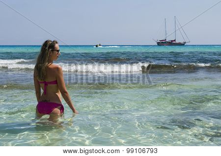 Blond Girl Looks Sailing Ship Sea Blue And Green To The Beach
