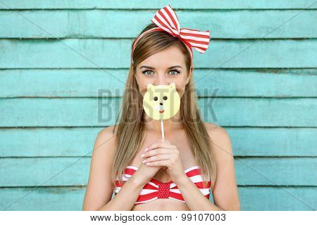 Beautiful girl with pretty smile holding hard candy on color wooden background