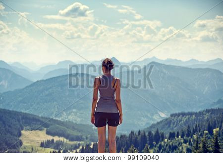 Young woman hiker standing admiring a mountaintop view looking out over distant ranges of mountains and valleys in a healthy active lifestyle concept