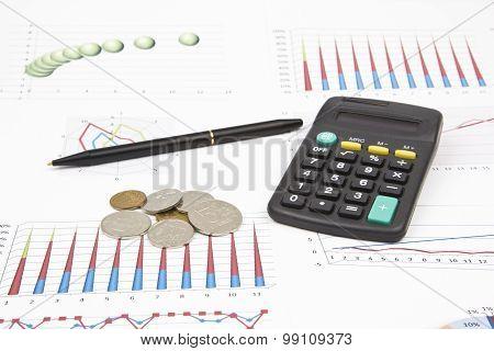 Business Still-life Of A Pen, Coin, Charts, Calculator