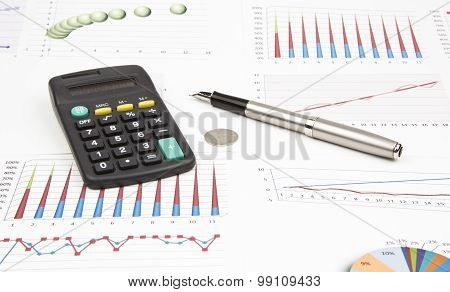 Business Still-life Of A Ink Pen, Coin, Charts, Calculator