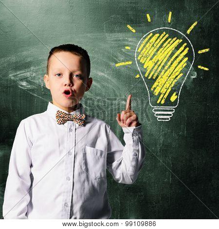 school boy is standing with blackboard behind him