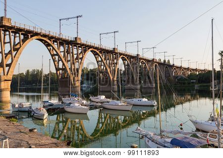 Old Openwork Reinforced Concrete Bridge And Sailboats At Dock.