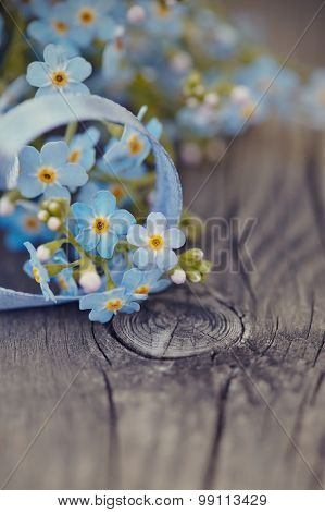 Forget-me-nots With A Blue Ribbon On A Wooden Table