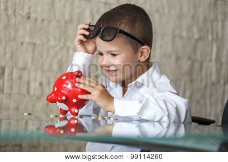 Happy Little Boy With Piggy Bank In Office