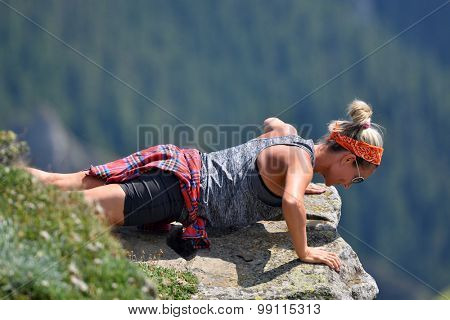 young athletic woman exercising on the mountain in summer