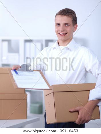 Delivery man with  parcel and a tablet standing in office