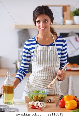 Young woman mixing fresh salad, standing near desk