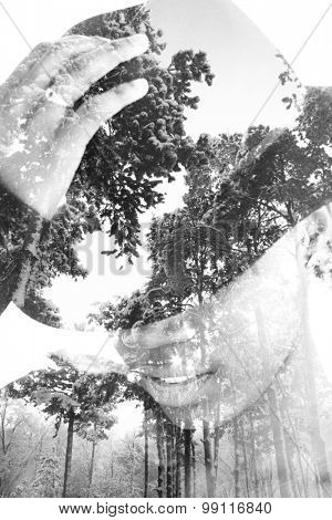 Multiple exposure portrait of woman wearing hat combined with photograph of trees covered with snow