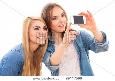 Young beautiful female friends making a selfie