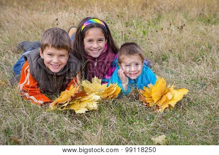 three kids with autumn leaves in park