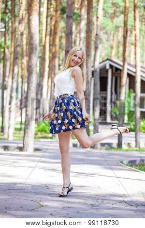 Full length of a beautiful young lady in skirt against summer forest background