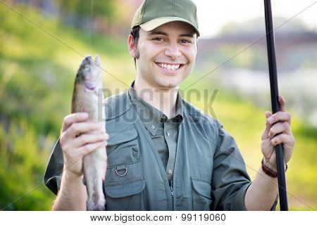 Portrait of a smiling fisherman holding a fish