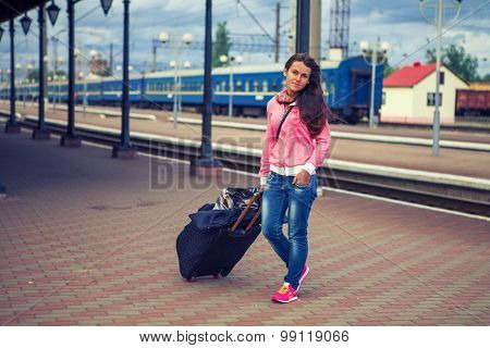a girl on train station waits a train