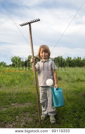 boy with a carrot and a watering can in the garden