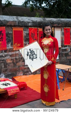 Vietnamese girl in Ao dai custome with ancient letter that an old master wrote for her in Hanoi, Vi