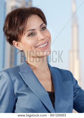 Portrait of beautiful smart business woman in the office on luxury buildings background, working in great successful company