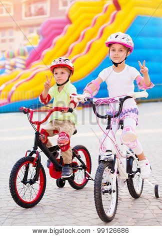 Happy friends on the bicycles, brother with sister having fun in amusement park, gesturing peace by hands, playing game outdoors, enjoying friendship and summer holidays
