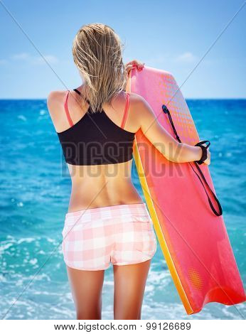 Back side of slim woman on the beach with body board in hands, having fun in summertime, active sportive lifestyle, summer holidays and vacation concept