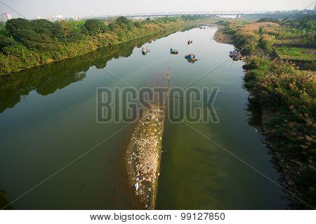 Red river (Hong river) under ancient Long Bien bridge in Hanoi, Vietnam