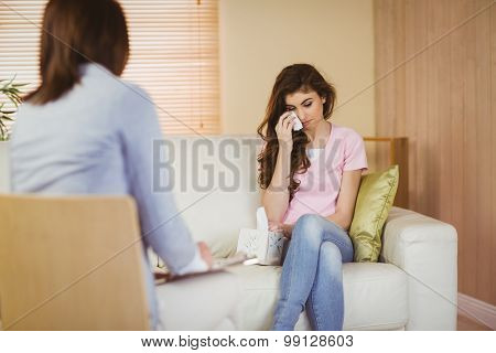 Therapist listening to her crying patient in therapists office