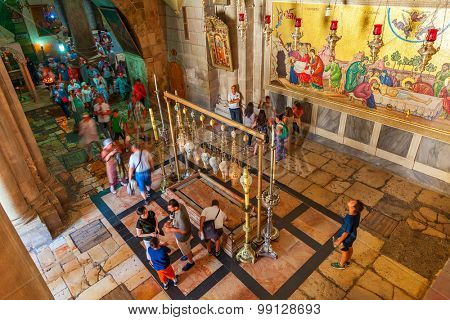 JERUSALEM. ISRAEL - JULY 16, 2015: People around Stone of Anointing and mosaic icon on the wall at the entrance to Holy Sepulcher church designate the place where Jesus' body was prepared for burial.