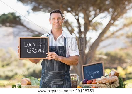 Portrait of a smiling farmer holding a locally grown sign