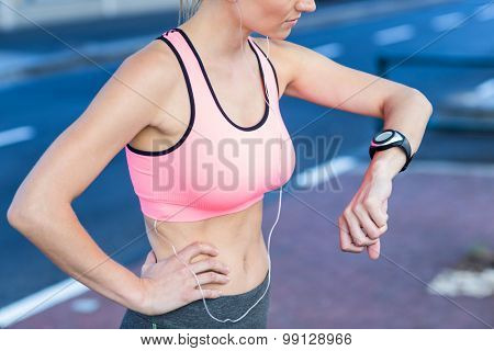 A beautiful athlete watching her watch on a sunny day