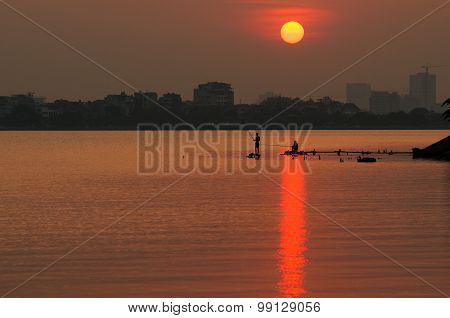 Fisherman in sunset in West Lake, Hanoi, Vietnam