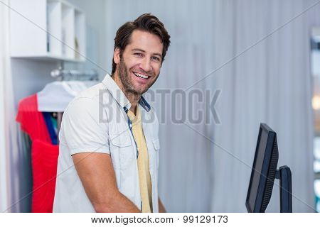 Portrait of smiling cashier in clothing store