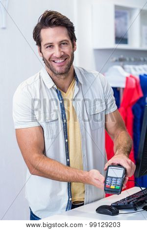 Portrait of smiling cashier showing credit card reader in clothing store