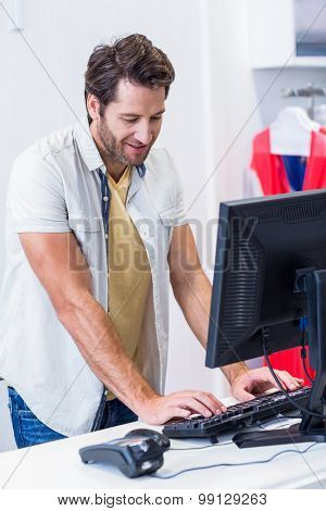 Smiling cashier typing in clothing store