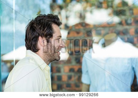 Smiling man going window shopping at shopping mall