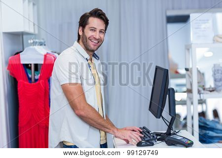 Portrait of smiling cashier typing in clothing store